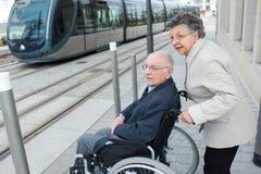 Uomo con la malattia sulla sedia a rotelle e sulla donna adorabile Immagine Stock