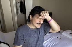 Uomo con la mano da dirigersi mentre sedendosi sul letto Immagini Stock Libere da Diritti