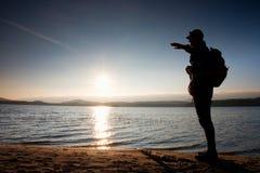 Uomo con la mano nell'aria La viandante alta in abiti sportivi scuri con i supporti sportivi dello zaino sulla spiaggia gode del  Immagine Stock Libera da Diritti