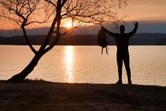 Uomo con la mano nell'aria La viandante alta in abiti sportivi scuri con i supporti sportivi dello zaino sulla spiaggia gode del  Fotografie Stock Libere da Diritti
