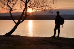 Uomo con la mano nell'aria La viandante alta in abiti sportivi scuri con i supporti sportivi dello zaino sulla spiaggia gode del  Fotografie Stock