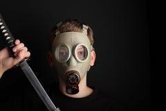 Uomo con la maschera antigas e la spada di katana su fondo nero Fotografia Stock