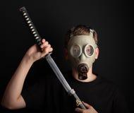 Uomo con la maschera antigas e la spada di katana su fondo nero Fotografie Stock