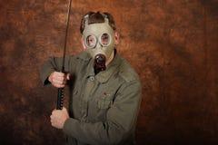 Uomo con la maschera antigas e la spada di katana sul fondo marrone del batik Fotografie Stock