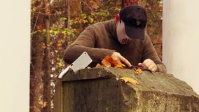 Uomo con la maschera spaventosa di Halloween che affila i coltelli in parco stock footage