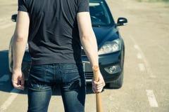 Uomo con la mazza da baseball sulla strada Immagini Stock Libere da Diritti