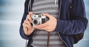 Uomo con la metà di sezione della macchina fotografica contro il pannello di legno blu confuso Fotografia Stock Libera da Diritti