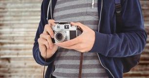 Uomo con la metà di sezione della macchina fotografica contro il pannello di legno confuso Immagini Stock Libere da Diritti