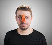Uomo con la molletta da bucato sul suo naso. fotografie stock