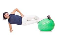 Uomo con la palla svizzera che fa gli esercizi Fotografie Stock Libere da Diritti
