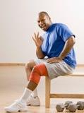 Uomo con la parentesi graffa di ginocchio che gesturing il simbolo giusto Fotografia Stock Libera da Diritti