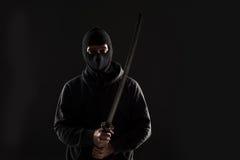 Uomo con la passamontagna e la spada di katana su fondo nero Fotografia Stock