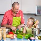 Uomo con la piccola figlia alla cucina immagine stock