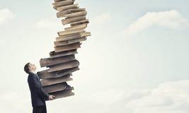 Uomo con la pila di libri in mani Immagine Stock