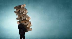 Uomo con la pila di libri in mani Fotografia Stock Libera da Diritti