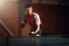 Uomo con la racchetta nell'azione, giocante ping-pong fotografia stock