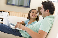 Uomo con la ragazza in salone con il computer portatile Fotografie Stock Libere da Diritti
