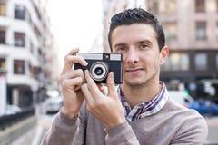 Uomo con la retro macchina fotografica nella via. Fotografie Stock