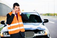 Uomo con la ripartizione dell'automobile che chiama la società di rimorchio Fotografia Stock