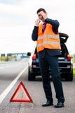 Uomo con la ripartizione dell'automobile che erige triangolo d'avvertimento Fotografie Stock