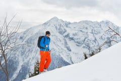 Uomo con la salita di alpinismo dello sci verso la sommità Fotografia Stock Libera da Diritti