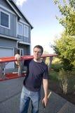Uomo con la scaletta ed il martello - verticale immagine stock