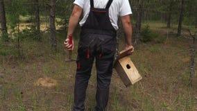 Uomo con la scatola di uccello in foresta