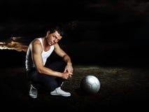 Uomo con la sfera di calcio che rimane sul terreno screpolato fotografie stock