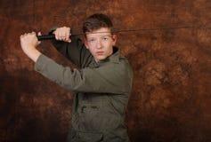 Uomo con la spada di katana sul fondo marrone del batik Fotografia Stock