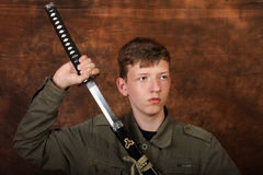 Uomo con la spada di katana sul fondo marrone del batik Fotografie Stock