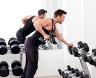 Uomo con la strumentazione di addestramento del peso su ginnastica di sport Immagini Stock