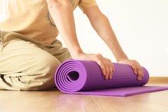 Uomo con la stuoia di yoga fotografia stock libera da diritti