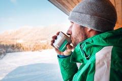 Uomo con la tazza dei wqrms caldi della bevanda sull'aria aperta di inverno Fotografie Stock Libere da Diritti