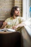 Uomo con la tazza di caffè che guarda attraverso la finestra in caffè Fotografie Stock Libere da Diritti