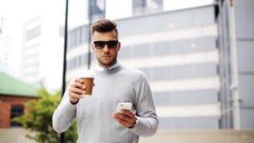 Uomo con la tazza di caffè e dello smartphone sulla via della città archivi video