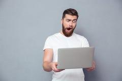 Uomo con la tazza stupida facendo uso del computer portatile Fotografia Stock