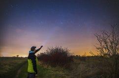 Uomo con la torcia elettrica osservando cielo notturno Immagini Stock Libere da Diritti