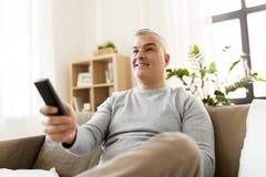 Uomo con la TV di sorveglianza telecomandata a casa Immagini Stock