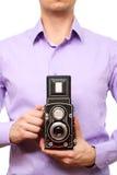 Uomo con la vecchia macchina fotografica della foto. immagine stock libera da diritti