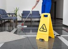 Uomo con la zazzera ed il segno bagnato del pavimento Fotografia Stock Libera da Diritti