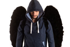Uomo con le ali nere in rivestimento grigio con il cappuccio lasciato la suoi condizione e sguardi della testa giù immagine stock