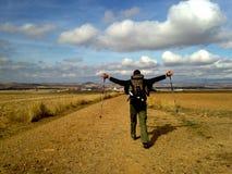 Uomo con le armi di diffusione e la camminata dello zaino nel campo Concetto di Camino de Santiago Concetto di pellegrinaggio immagine stock libera da diritti