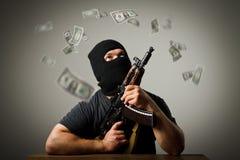 Uomo con le banconote del dollaro e della pistola Immagini Stock