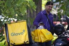 Uomo con le borse di Glovo che lavorano al servizio di distribuzione dell'alimento fotografia stock libera da diritti