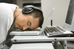 Uomo con le cuffie che dorme sul computer portatile. Fotografie Stock Libere da Diritti