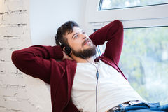 Uomo con le cuffie che si rilassano sulla sedia Fotografie Stock