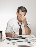 Uomo con le fatture di pagamento di emicrania Fotografie Stock Libere da Diritti