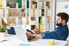 Uomo con le gambe sullo scrittorio in ufficio fotografie stock
