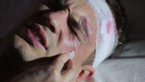 Uomo con le lesioni alla testa che si trovano sul letto Cure dell'infermiere per un uomo danneggiato video d archivio