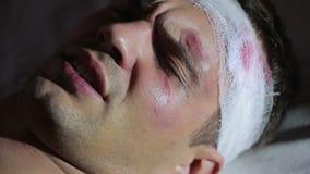 Uomo con le lesioni alla testa che si trovano sul letto Testa bendata contusione sul suo fronte video d archivio